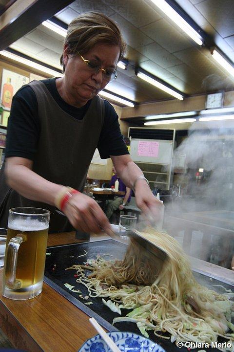 un uomo prepara gli yakisoba